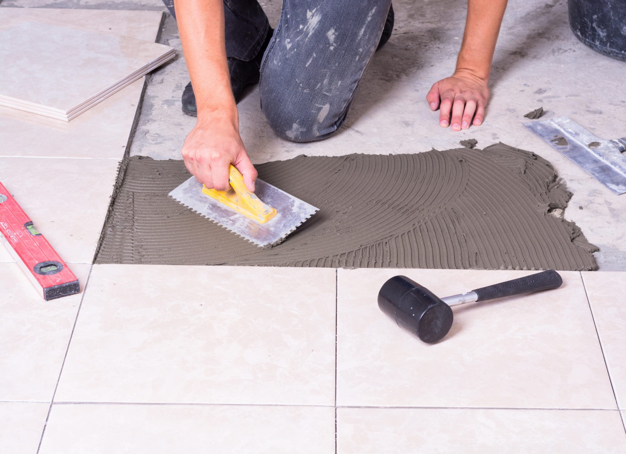 Tiler using tools to install ceramic tiles on a floor